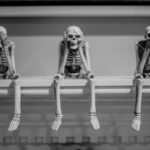 three wise sitting human skeleton figurines on white shelf