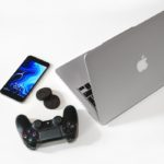 silver MacBook beside black Sony game pad