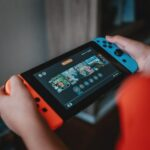 person holding black and orange nintendo switch